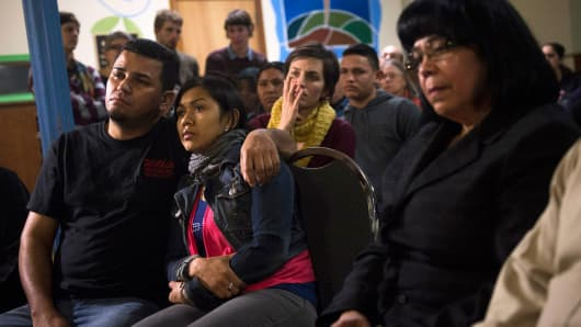 Undocumented immigrant Angela Navarro and her husband Ermer Fernandez (L), along with other immigrants and supporters, watch President Barack Obama announce executive action on immigration, at the West Kensington Ministry church, in Philadelphia, Nov. 20, 2014.