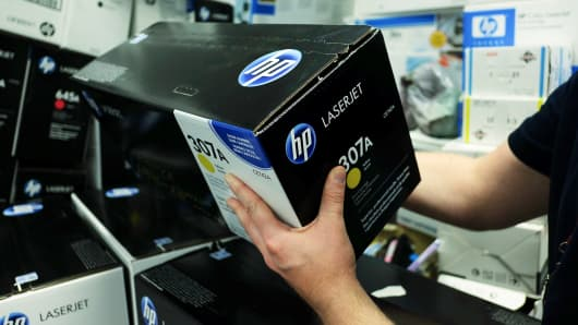 An employee selects an HP laserjet printer cartridge, by Hewlett-Packard Co.