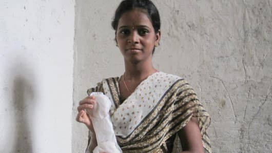 A young woman from Saathi's pilot village in India holds a Saathi pad.