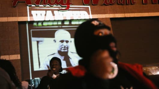 Demonstrators project a wanted poster with a picture of Police Officer Darren Wilson on a wall near the police station amid protests in the wake of 18-year-old Michael Brown's death in Ferguson, Missouri.