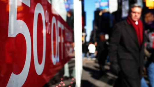 People walk past a store displaying a discount sign in New York on Nov. 21, 2014.