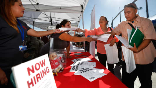 Attendees pick up leaflets at a military veterans' job fair in Carson, California.