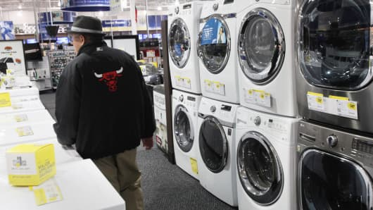 A shopper walks past washer and dryers at a Best Buy store in Northbrook, Illinois.