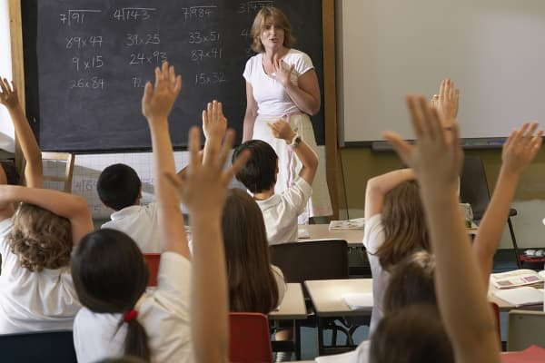 Students with hands raised in classroom