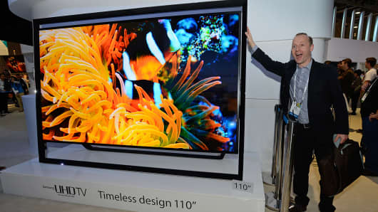 An attendee poses next to Samsung's 110-inch UHD television at the 2014 International CES at the Las Vegas Convention Center.