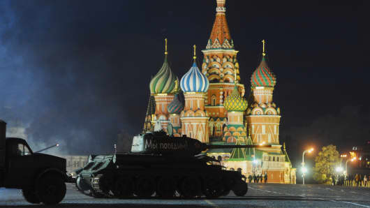 Military vehicles drive past St. Basil's Cathedral during a rehearsal for the anniversary of a historical World War II parade in Moscow's Red Square, Nov. 1, 2014.