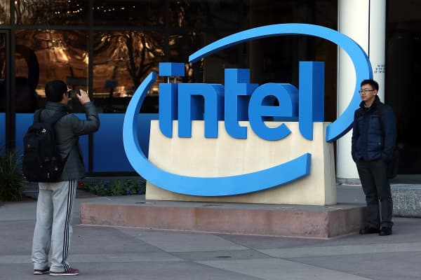 Visitors take pictures next to the Intel logo outside of the Intel headquarters in Santa Clara, Calif.