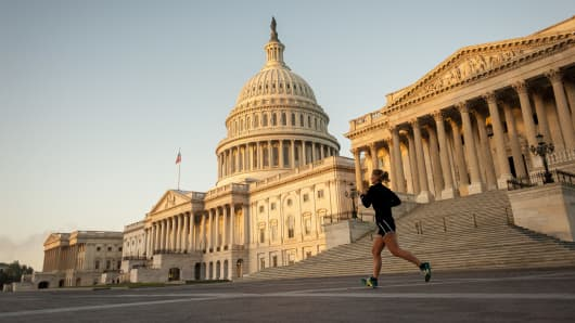 A jogger runs past the United States Capitol building at sunrise in Washington, D.C.