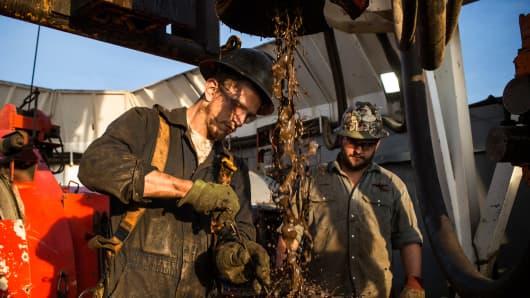 Floor hands work on an oil rig in the Bakken shale formation outside Watford City, North Dakota.