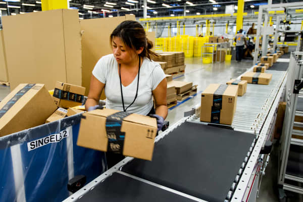 An Amazon.com Inc. employee lifts a box from a conveyor at the company's fulfillment center in Tracy, California