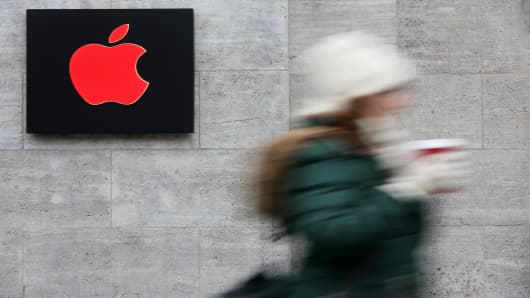 A pedestrian passes a red Apple logo at the Apple Store on Dec. 1, 2014 in Berlin.