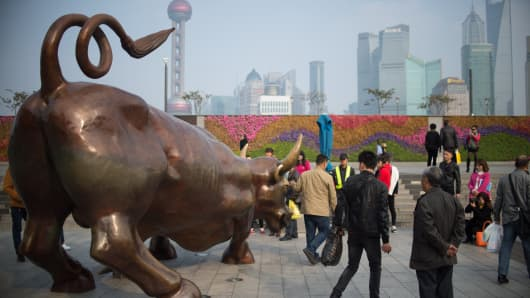People have photos taken with a replica of the famous Wall Street bronze bull on the Bund in Shanghai.