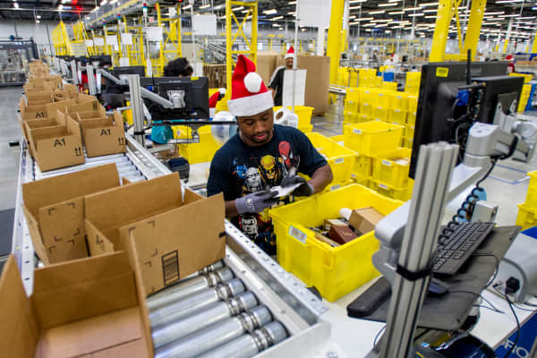 Amazon employees load boxes with orders at the company's fulfillment center ahead of Cyber Monday in Tracy, Calif.