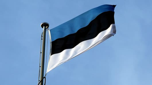 The Estonian nation flag flies from the top of the parliament building in Tallinn, Estonia.