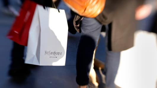 A customer carries an Yves Saint Laurent-branded shopping bag in Rome, Italy.