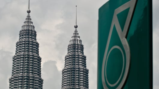 Malaysia's iconic Twin Towers are seen in the background of the Malaysian oil and gas company Petronas logo at a petrol station in Kuala Lumpur