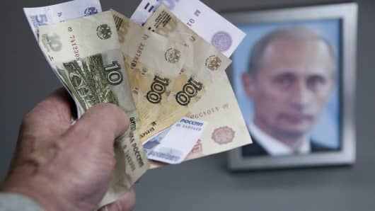 Russian rubles on display in front of a portrait of Russian President Vladimir Putin.