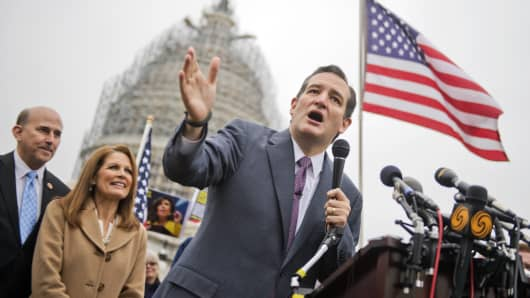 Sen. Ted Cruz, R-Texas, speaks at the podium as Reps. Louie Gohmert, R-Texas, and Michelle Bachmann, R-Minn., look on, during a rally on the east front lawn of the Capitol to call for the defunding of President Obama's executive action that grant's amnesty to illegal immigrants, December 3, 2014.