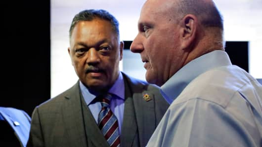 The Reverend Jesse Jackson (L) and former Microsoft Chief Executive Steve Ballmer attend the annual shareholders' meeting in Bellevue, Washington December 3, 2014.