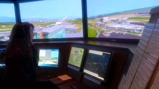 A student at Dowling College training in an air traffic control simulator.