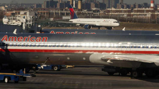 Two American Airlines Inc. jets sit parked at gates while a Delta Air Lines Inc. plane taxis down the runway at LaGuardia Airport in the Queens borough of New York.