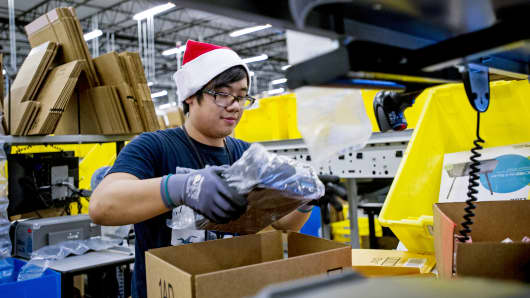 An Amazon.com employee loads merchandise into a box at the company's fulfillment center in Tracy, Calif., Nov. 30, 2014.