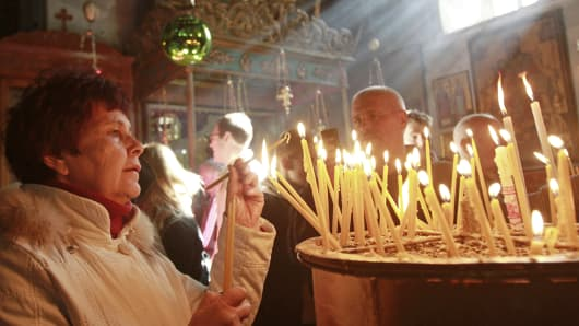 A Christian pilgrim lights a candle in the Church of the Nativity, traditionally believed to be the birthplace of Jesus Christ, in the West Bank biblical town of Bethlehem.