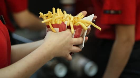 An employee collects two portions of french fries for a customer inside a Burger King fast food restaurant.