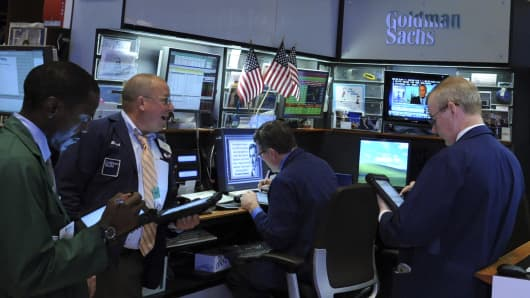Traders work at the Goldman Sachs Group booth on the floor of the New York Stock Exchange.