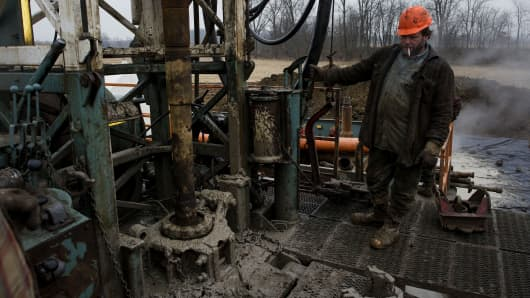 A rig hand works the controls while changing out a drill pipe at a Knox Energy Inc. oil drilling site in Knox County, Ohio.