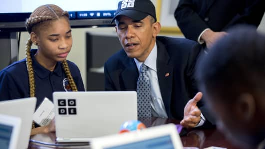 President Barack Obama participates in an 'Hour of Code' event with middle-school students including Adrianna Mitchell in the Eisenhower Executive Office Building next to the White House in Washington, D.C.