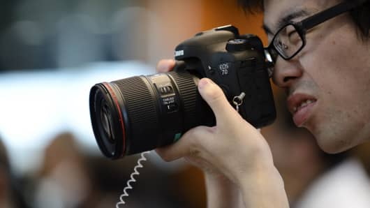 An attendee tries the Canon Inc. EOS 7D Mark II digital single lens reflex (DSLR) camera during its unveiling in Tokyo, Japan.