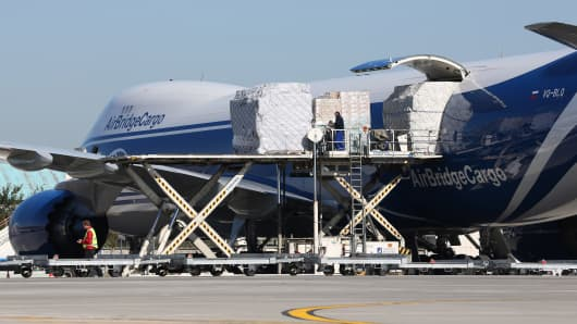 Airport handlers unload freight from a Boeing 747-8F jet freighter operated by AirBridgeCargo.