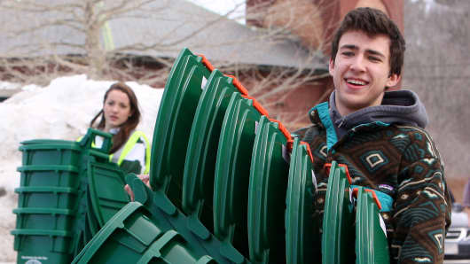 Hannah Parker, left, and Seth Cohen carry curbside compost bins to truck as town residents gathered at a town garage to distribute curbside composting bins to homes in Manchester-by-the-Sea, Mass. on March 8, 2014.