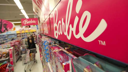 A customer browses the Mattel Barbie dolls section of a now closed Toys 'R' Us store.