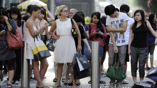 Shoppers wait at a pedestrian junction to cross a road, in Singapore,