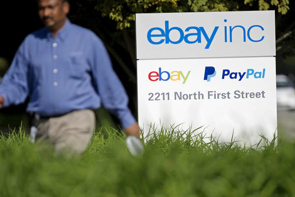 A pedestrian walks past a sign displayed at eBay headquarters in San Jose, Calif., Sept. 30, 2014.