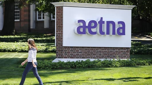 A pedestrian walks past a sign for Aetna Inc., at the company headquarters in Hartford, Conn.