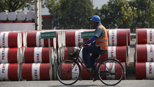 An employee rides his bike past barrels of petroleum products at a state-owned Pertamina fuel depot in Jakarta, Indonesia.