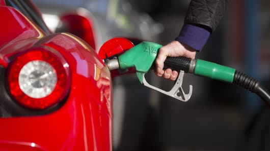 A driver refuels his luxury Ferrari automobile with unleaded petrol at an Esso gas station, operated by Exxon Mobil Corp., in Guildford, U.K.