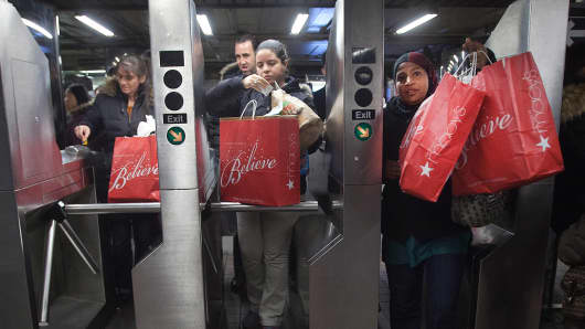 Shoppers enter the 34th Street subway station with Macy's packages in New York.
