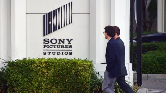 Pedestrians walk past Sony Pictures Studios in Los Angeles, Dec. 4, 2014.
