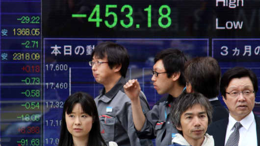 Pedestrians pass before a share prices board in Tokyo, Japan.