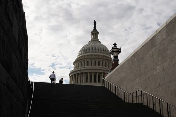 Late-afternoon visitors climb a stairway outside the U.S. Capitol in Washington.