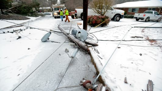 Power company crews work on a downed power line near Emory University after the weight of accumulating freezing rain, sleet and snow toppled a nearby tree that slammed into power poles during a winter storm Feb. 12, 2014, in Atlanta.
