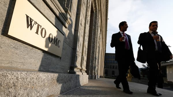 Delegates walk outside the World Trade Organization (WTO) headquarters in Geneva.