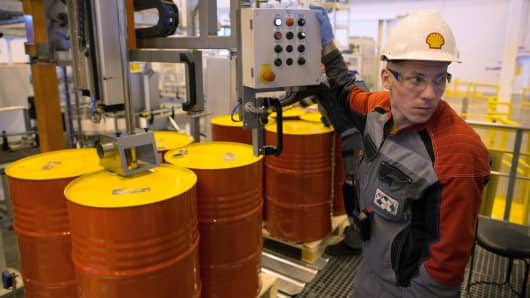 An employee holds a control panel as barrels are filled with lubricant oil ahead of shipping at Royal Dutch Shell lubricants blending plant in Torzhok, Russia.