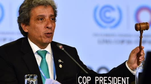 COP20 President and Peruvian Minister of Environment Manuel Pulgar slams his mallet on December 14, 2014, to approve and close the discussion on a proposed compromise document handed out during the marathon UN talks in Lima