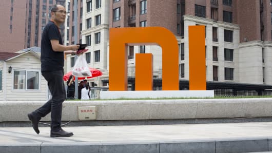 A man walks past a Xiaomi logo displayed outside the company's headquarters in Beijing on Friday, Sept. 12, 2014.