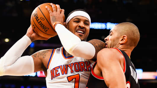 Nicolas Batum of the Portland Trail Blazers guards Carmelo Anthony of the New York Knicks at Madison Square Garden on December 7, 2014 in New York City.